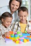 Portrait de la mère et des enfants jouant avec les blocs en plastique colorés ensemble images stock