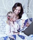 Portrait de la mère et de la fille s'étendant dans la lecture de lit et l'écriture, concept de personnes de mode de vie Photographie stock libre de droits