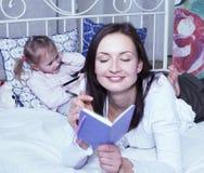 Portrait de la mère et de la fille s'étendant dans la lecture de lit et l'écriture, plan rapproché de concept de personnes de mod Photos stock