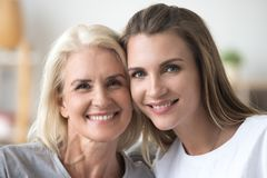 Portrait de la mère et de la fille de sourire posant pour le pictur de famille image libre de droits