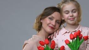 Portrait de la mère et de la fille tenant l'humeur de tulipes, de féminité et de ressort clips vidéos