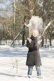 Portrait de la neige de lancement de belle fille pendant l'hiver La jeune femme heureuse joue avec une neige dans le jour d'hiver image stock