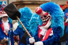 Portrait of masked person with blue wig parading in the street