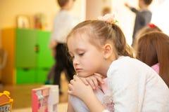 Portrait de la petite fille blonde triste s'asseyant dans le jardin d'enfants photos stock