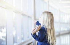 Portrait de la petite fille blonde utilisant la veste bleue dans l'immeuble de bureaux Photo libre de droits