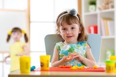 Portrait de la petite fille d'achild faisant le jouet avec de la pâte à modeler Photos stock