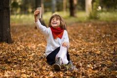 Portrait de la petite fille drôle grimaçant tout en prenant le selfie au-dessus de l'automne photo stock