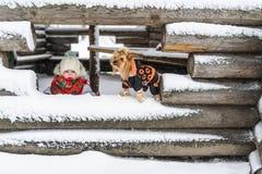 Portrait de la petite fille et du petit chien dans la perspective de la maison couverte de neige non finie dans le village Image stock