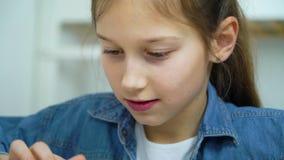 Portrait de la petite fille heureuse jouant des jeux sur Internet sur le comprimé banque de vidéos