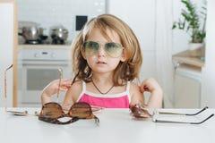 Portrait de la petite fille mignonne essayant de porter des lunettes photo stock