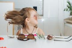 Portrait de la petite fille mignonne essayant de porter des lunettes image libre de droits