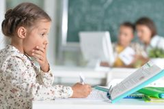 Portrait de la petite fille mignonne s'asseyant dans la salle de classe image stock