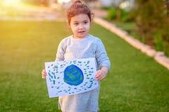 Portrait de la petite fille mignonne tenant le globe de dessin de la terre Drawnig d'enfant une image de la terre photographie stock libre de droits