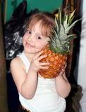 Portrait de la petite fille de sourire avec un grand ananas photos libres de droits