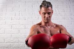 Portrait de la position belle d'homme de boxeur sur le mur bric et de regarder la cam?ra avec le regard fixe intense photographie stock
