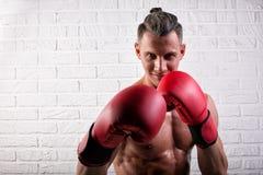 Portrait de la position belle d'homme de boxeur sur le mur bric et de regarder la cam?ra avec le regard fixe intense photo stock