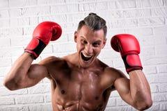 Portrait de la position belle d'homme de boxeur sur le mur bric et de regarder la cam?ra avec le regard fixe intense images libres de droits