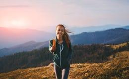 Portrait de la position heureuse de randonneur de femme sur le bord de l'arête de montagne sur le fond du coucher du soleil Voyag image stock