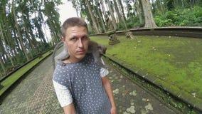 Portrait de la position mignonne d'homme en parc avec le singe se reposant sur ses épaules banque de vidéos
