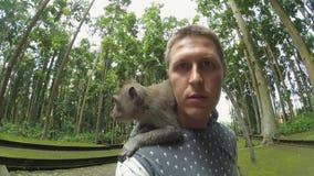Portrait de la position mignonne de type en parc avec le singe acéré sur ses épaules banque de vidéos