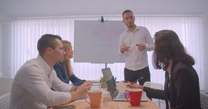 Portrait de la réunion de quatre collleagues dans le bureau à l'intérieur Idées d'écriture d'homme d'affaires sur le tableau blan banque de vidéos