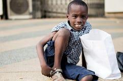 Portrait de la séance et du sourire de petit garçon Photographie stock