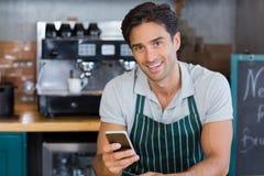 Portrait de la serveuse de sourire à l'aide du téléphone portable images libres de droits