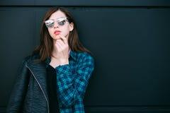 Portrait de la veste en cuir de port de fille de brune se tenant dehors dans la ville contre le mur urbain noir Photos stock