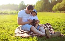 Portrait de la vie du père et du fils s'asseyant ensemble sur l'herbe Photos stock