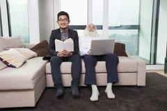 Portrait de livre de lecture de petit-fils tandis que grand-père à l'aide de l'ordinateur portable sur le sofa à la maison Image libre de droits