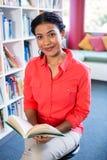 Portrait de livre de lecture de professeur à la bibliothèque à l'école photo libre de droits