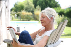 Portrait de livre de lecture supérieur de femme dehors Photographie stock libre de droits