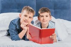 portrait de livre de lecture de petits garçons tout en se trouvant sous la couverture photographie stock