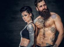 Portrait de mâle et de femelle barbus sans chemise et tatoués de brune avec l'encre de tatouage sur son torse Photos libres de droits