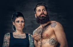 Portrait de mâle et de femelle barbus sans chemise et tatoués de brune avec l'encre de tatouage sur son torse Images stock