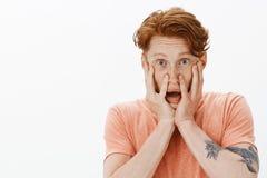 Portrait de mâle mignon intense et préoccupé choqué avec des taches de rousseur, tatouages et cheveux de gingembre, tenant des pa photographie stock libre de droits