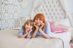 Portrait de mère avec sa petite fille sur un lit Images stock