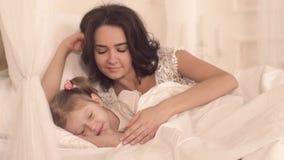 Portrait de mère de soin mettant sa petite fille mignonne pour dormir clips vidéos