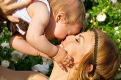 Portrait de mère et d'enfant heureux sur un fond des fleurs Photo libre de droits