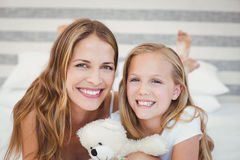Portrait de mère et de fille de sourire sur le lit à la maison Image libre de droits