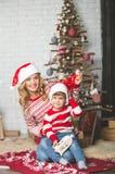 Portrait de mère et de fils heureux sur le fond de l'arbre de Noël dans la pièce de nouvelle année L'idée pour des cartes postale Photos libres de droits