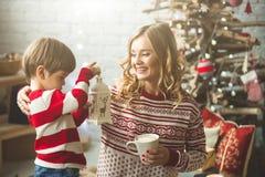 Portrait de mère et de fils heureux sur le fond de l'arbre de Noël dans la pièce de nouvelle année L'idée pour des cartes postale Photographie stock libre de droits