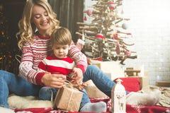 Portrait de mère et de fils heureux sur le fond de l'arbre de Noël dans la pièce de nouvelle année L'idée pour des cartes postale Image libre de droits
