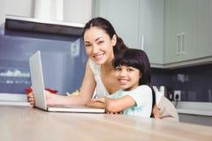 Portrait de mère heureuse et de fille travaillant sur l'ordinateur portable photo libre de droits