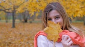 Portrait de Madame In A Beige Coat et jeux oranges d'écharpe avec Autumn Yellow Leaf image libre de droits