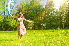 Portrait de Madame caucasienne heureuse positive Running en parc d'été avec le foulard de vol photo stock
