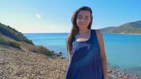 Portrait de main courante de belle jeune femme par des cheveux soufflant en vent sur le fond de la plage méditerranéenne lent banque de vidéos