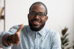 Portrait de main de offre de sourire amicale d'homme d'affaires africain pour la salutation photographie stock libre de droits