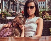 Portrait de maman à la mode et de sa belle fille pendant un moment dans un café extérieur Photographie stock