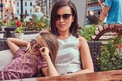 Portrait de maman à la mode et de sa belle fille pendant un moment dans un café extérieur Image libre de droits